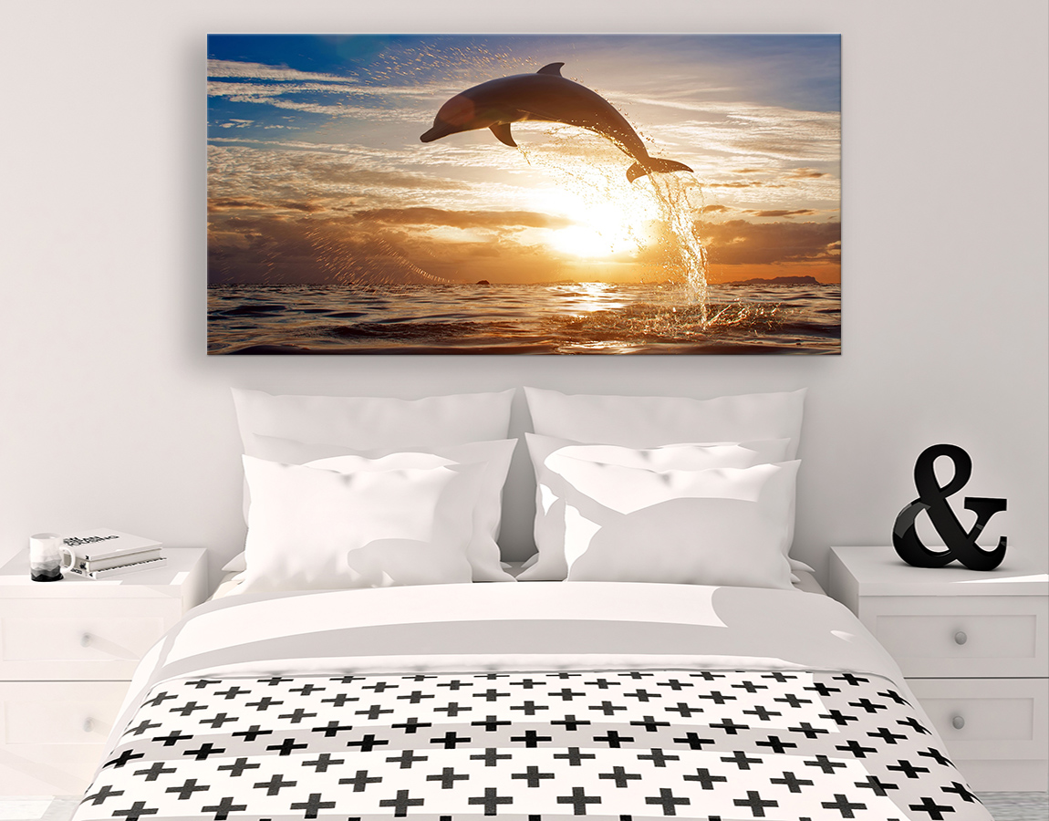 Dolphin jumping into sunrise